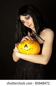 Strange woman in black dress holding halloween pumpkin