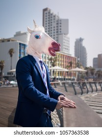 Strange young man stands on city promenade. Stylish unicorn relaxes in warm sunny day