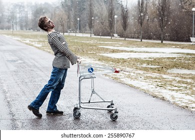 Strangely walking guy with a shopping wagon