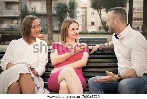 Stranger man is talking with young females who are resting together in the park.