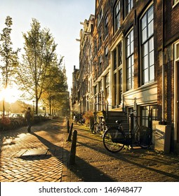A stranger in the streets of the city Amsterdam, accompanied by long shadows, strolled between the canals and residential houses during this atmospheric sunset.