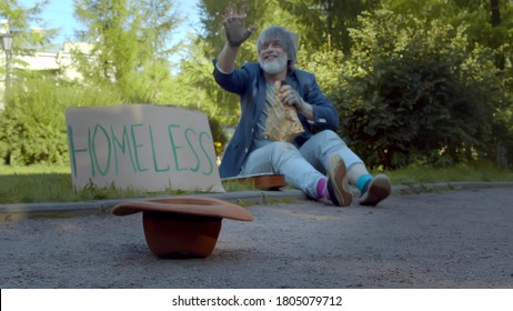 Strangers giving money to homeless beggar sitting on ground in city park. Poor old man waving hand thanking eople for putting banknotes in hat sitting on street with cardboard sign