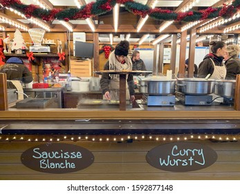 Strasbourg, Alsace/ France - December 1, 2019. Saleswoman in the shop with traditional food and curry wurst sausages on the Christmas market