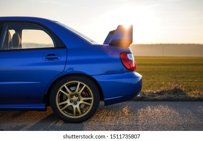 Strasbourg, FRANCE - 06 JULY 2018: Subaru STI 2003 type UK driving in the backcountry at sunset. Rear view with big spoiler.