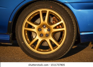 Strasbourg, FRANCE - 06 JULY 2018: Subaru STI 2003 type UK driving in the backcountry. Gold rim close up.
