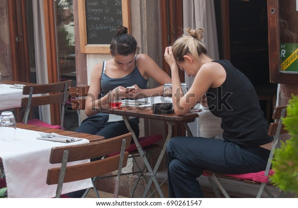 STRASBOURG - France - 1 August 2017 - two women with smart phone in restaurant terrace
