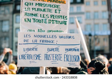 STRASBOURG, FRANCE - 11 JAN, 2015:  People hold placard reading 'Liberalism, Austerity, Exclusion' during a unity rally (Marche Republicaine) where 50000 took part in tribute three-day killing spree