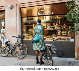 STRASBOURG, FRANCE - 13 MAR, 2018: Fashionable woman in green coat parking bike in front of French boulangerie Au Pain de Mon Grand-Pere on France street