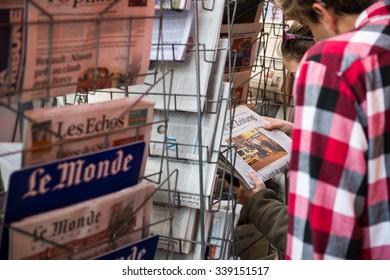 STRASBOURG, FRANCE - 14 NOV, 2015: People reading front kovers at press kiosk of International newspapers display headlining the terrorist attacks yesterday in Paris