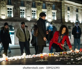 STRASBOURG, FRANCE - 14 NOV 2015: Woman light candles in the center of Strasbourg for the victims of the November 13 attacks in Paris that killed at least 128 people