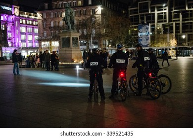 STRASBOURG, FRANCE - 14 NOV 2015: Police officers on bike looking at people and candles during a vigil in the center of Strasbourg for the victims of the November 13 attacks in Paris