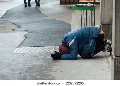 Strasbourg - France - 24 November 2018 -  poor man  with plastic cup in hands prostrate in the street