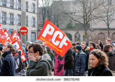 STRASBOURG, FRANCE - 9 MAR 2016: French communist flags waving as thousands of people demonstrate as part of nationwide day of protest against proposed labor reforms by Socialist Government
