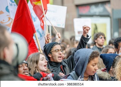 STRASBOURG, FRANCE - 9 MAR 2016 Protester with raised hands in front row of thousands of people demonstrating as part of nationwide day of protest against proposed labor reforms by Socialist Government