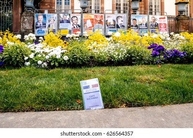 STRASBOURG, FRANCE - APR 23, 2017: Carte Electorale - voter's card French voter registration card is seen in front of official campaign posters for all eleven candidates for the 2017 French elections