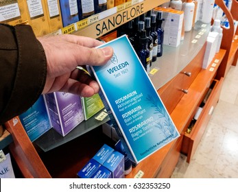 STRASBOURG, FRANCE - APR 24, 2017: Point of view of man buying Weleda Tonic bath gel in drug store pharmacy store shopping