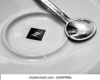 STRASBOURG, FRANCE - APR 27, 2017: Nespresso logotype on coffee plate with silver spoon - black and white image. Nespresso is the brand name of Nestle Nespresso S.A. operating unit of the Nestle Group
