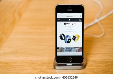 STRASBOURG, FRANCE - APR 9, 2016: New iPhone SE in docking station with Apple.com Watchpage opened. New Apple iPhone tends to become one of the most popular smart phones in the world.