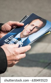 """STRASBOURG, FRANCE - APRIL 29, 2017 : Political activists for the """"En Marche !"""" movement distributing campaign flyers for the second round of the french presidential election."""