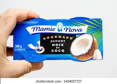 Strasbourg, France - Aug 11, 2018: Man hand holding Mamie Nova Gourmand Coconut yogurt pack