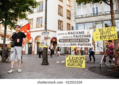 STRASBOURG, FRANCE - AUG 22 2015: People protesting against immigration policy and border management which asks for commitment of migrants boat disasters - man protesting with placards and flag