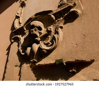 Strasbourg, France, August 2019. A low relief with a skull on a street in the historic center.