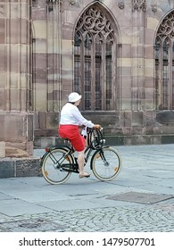 STRASBOURG, FRANCE - AUGUST 3, 2019: Woman in red skirt riding a bicycle by old cathedral in Strasbourg August 3, 2019 in Strasbourg, France