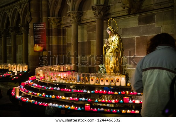 STRASBOURG, FRANCE - CIRCA 2018: Woman with candles memories faith in Strasbourg Notre-Dame cathedral with statue of Mary praying