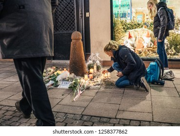 STRASBOURG, FRANCE - DEC 13, 2018: Young girls lighting candles on Rue des Orfevres to attend a vigil with multiple light candles flowers and messages for the victims of terrorist Cherif Chekatt at