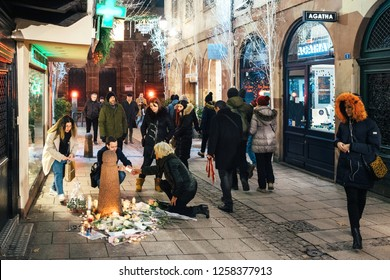 STRASBOURG, FRANCE - DEC 13, 2018: Sad people mourners gathered on Rue des Orfevres to attend a vigil with multiple light candles flowers and messages for the victims of terrorist Cherif Chekatt at