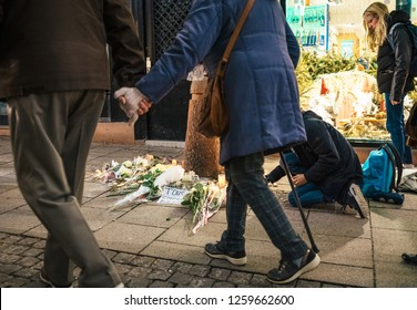 STRASBOURG, FRANCE - DEC 13, 2018: Senior couple holding hands walking near mourning place on Rue des Orfevres to attend a vigil with multiple light candles flowers and messages after terrorist attack
