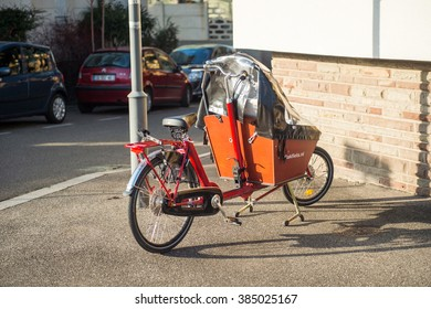 STRASBOURG, FRANCE - DEC 25, 2015: Cargo bike with protect tent parked on the street. The cargobike made by Bakfiets netherlands is a transport bicycle that's user friendly