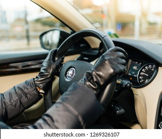 STRASBOURG, FRANCE - DEC 26, 2018: Woman driving Skoda Octavia Czech car wearing leather gloves focus on the car logotype on the steering wheel
