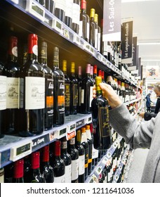 STRASBOURG, FRANCE - DEC 30, 2017: Elegant French woman buying red wine alcoholic drinks wines, champagne and whiskey in wine department of a large French supermarket