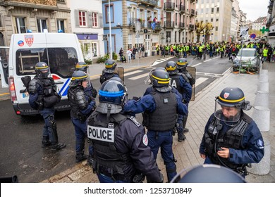 STRASBOURG, FRANCE - DEC 8, 2018: Police officers securing the zone in front of the Yellow vests movement protesters on Quai des Bateliers street