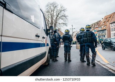 STRASBOURG, FRANCE - DEC 8, 2018: Rear view of CRS French Police officers securing the zone in front of the Yellow vests movement protesters on Quai des Bateliers street