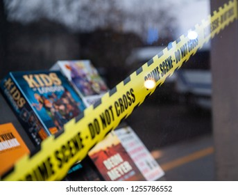 STRASBOURG, FRANCE - DEC 8, 2018: Police scene do not cross sign on the store selling diverse books in central place of city of Strasbourg with reflection of the police sirens lights