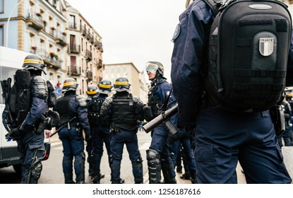 STRASBOURG, FRANCE - DEC 8, 2018: French Police officers securing the zone in front of the yellow vests protesters on Quai des Bateliers street woman officer with tear gas bottle ready to use it - squ