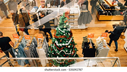 STRASBOURG, FRANCE - DEC 9, 2016: View from the street of clothing shop with Christmas tree and people buying gifts