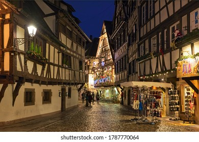 STRASBOURG, FRANCE - DECEMBER 15, 2019: Rue du Bain-aux-Plantes street in Petite France historic quarter in dusk with half-timbered houses decorated for Christmas.