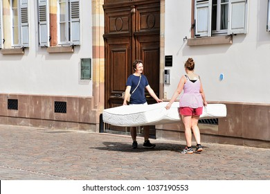 Strasbourg, France / Europe - August 5, 2017: young couple transporting a white bed mattress on cobblestone street in Strasbourg France