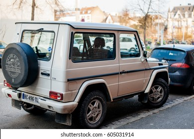 STRASBOURG, FRANCE - FEB 13, 2017: Rear view of white luxury white Mercedes-Benz G-Class suv parked on French street.  The G-Class is a mid-size four-wheel drive luxury SUV