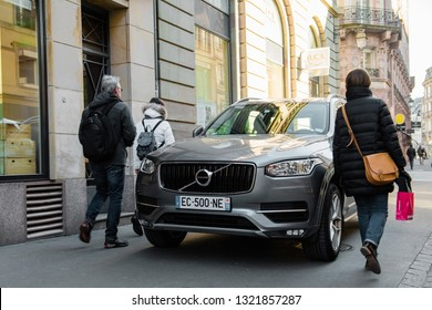 Strasbourg, France - Feb 16, 2018: People walking early in the morning on Rue De La Mesange near Boutique, traiteur Edouard Artzner with luxury Volvo XC90 SUV parked on the trottoir