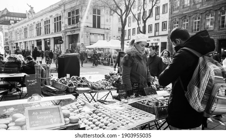 Strasbourg, France - Feb 23, 2018: People pedestrians buying at the outdoor market stall bagels french croissants and other bakeries from Paul pastries store boulangeries - black and white image