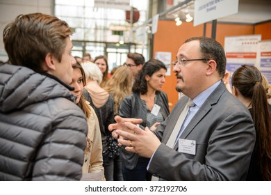 STRASBOURG, FRANCE - FEB 4, 2016: Children and teens of all ages attending annual Education Fair to choose career path and receive vocational counseling - professor explaining