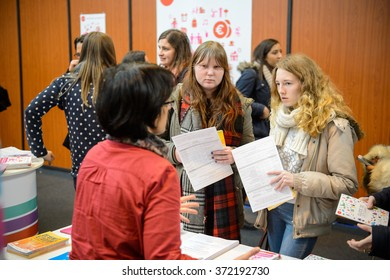 STRASBOURG, FRANCE - FEB 4, 2016: Children and teens of all ages attending annual Education Fair to choose career path and receive vocational counseling - friends receiving advice