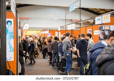STRASBOURG, FRANCE - FEB 4, 2016: Children and teens of all ages attending annual Education Fair to choose career path and receive vocational counseling - rows of college stands