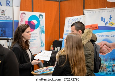 STRASBOURG, FRANCE - FEB 4, 2016: Children and teens of all ages attending annual Education Fair to choose career path and receive vocational counseling - teens receiveing advices at stand