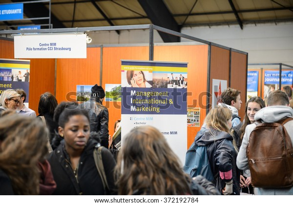 STRASBOURG, FRANCE - FEB 4, 2016: Children and teens of all ages attending annual Education Fair to choose career path and receive vocational counseling - Management and MArketing lyceum stand