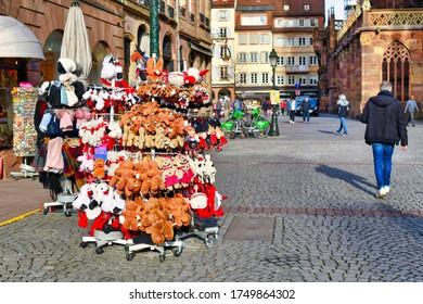 Strasbourg, France - February 2020: Racks with Alsace region souvenirs like plush storks or gingerbread men